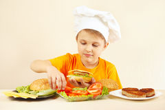 Little boy in chefs hat puts tomato on hamburger Stock Photo