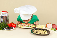 Little boy in chefs hat sniffing cooked pizza Stock Photography