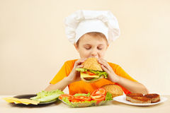 Little boy in chefs hat is tasting cooked hamburger Stock Photos
