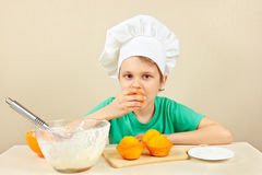 Little boy in chefs hat is tasting cooked homemade cake Stock Photo