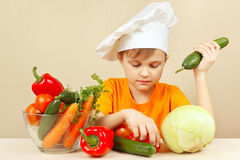 Little boy in chefs hat with vegetables at table Royalty Free Stock Photo