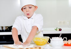 Little boy in chefs uniform baking in the kitchen Stock Photo