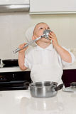 Little boy in chefs uniform licking a ladle Stock Photography