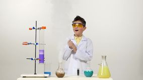 Little boy chemist in uniform, protective glasses stock video