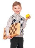 Little boy with chessboard. Emotional portrait of caucasian little boy with chessboard and apple. Funny child holding a game of chess in his arms while laughing Royalty Free Stock Photos