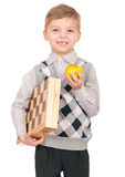 Little boy with chessboard. Emotional portrait of caucasian little boy with chessboard and apple. Funny child holding a game of chess in his arms while laughing Royalty Free Stock Image