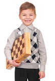 Little boy with chessboard. Emotional portrait of caucasian little boy with chessboard. Funny child holding a game of chess in his arms while laughing. Cute Royalty Free Stock Photos