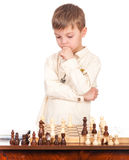 Little boy with chessboard. Emotional portrait of caucasian little boy with chessboard. Funny child thinking hard on chess combinations. Cute smart kid playing Stock Photo