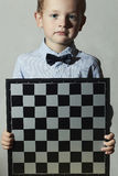 Little boy with chessboard.fashion children.Little genius Child.Intelligent Royalty Free Stock Photography