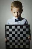 Little boy with chessboard.Intelligent game.Emotion. Serious Royalty Free Stock Photos