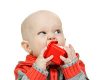 Little boy chewing on a plastic pyramid Stock Images