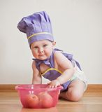 Little boy in a chief hat and aprons cooking. Little boy in a chief hat and aprons sitting on a floor near bowl with apples Stock Image