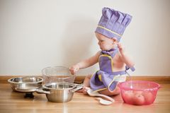 Little boy in a chief hat and aprons cooking. Little boy in a chief hat and aprons sitting on a floor among pans and bowls Stock Photography