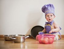 Little boy in a chief hat and aprons sitting on a floor. Among pans and bowls Stock Image