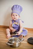 Little boy in a chief hat and aprons sitting on a floor. Little boy in a purple chief hat and aprons cooking at the kitchen near pan Stock Image