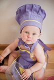 Little boy in a chief hat cooking. Baby in a purple chief hat and aprons sitting on the floor Stock Images