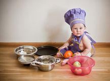 Little boy in a chief hat cooking. Baby in a purple chief hat and aprons sitting on the floor among pans and bowls Royalty Free Stock Photography