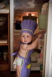 Little boy in a chief hat standing near refrigerator Stock Photos