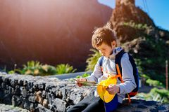 Little boy child with backpack reading map Royalty Free Stock Image