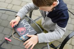 Little boy child drawing a love declaration. On small blackboard for his mother on Mother's Day royalty free stock image