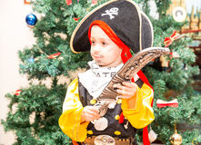 Little boy child dressed as pirate for Halloween  on background of Christmas tree. Royalty Free Stock Photos