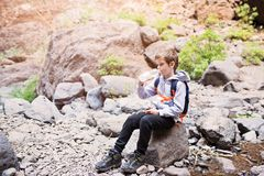 Little boy child drinking bottled mineral water on mountain trail. Mountain adventure. Masca Valley, Tenerife island, Canary Islands, Spain royalty free stock photo