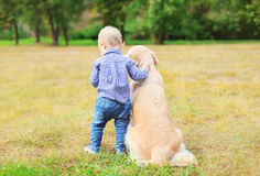 Little boy child and Golden Retriever dog together outdoors. Back view royalty free stock images