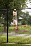 Little Boy Child Hanging From High Chain Link Fence Trying to Cl royalty free stock photos