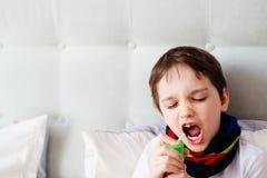 Little boy child inhaling his throat with spray inhaler Stock Photos