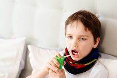 Little boy child inhaling his throat with spray inhaler Stock Images