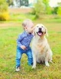 Little boy child kissing Golden Retriever dog on grass Stock Photos