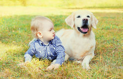 Little boy child lying with Golden Retriever dog on grass. In park royalty free stock photography