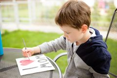 Little boy child painting greeting card for his mother Stock Photo