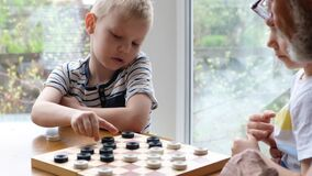 Little boy child play checkers with grandfather