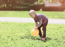 Little boy child playing with ball outdoors on the grass Stock Photo