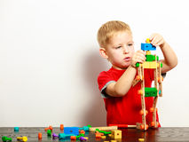 Little boy child playing with building blocks toys interior. Royalty Free Stock Image