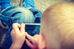 Little boy child playing games on mobile phone outdoor Royalty Free Stock Photo