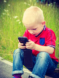Little boy child playing games on mobile phone outdoor Stock Photography