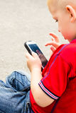 Little boy child playing games on mobile phone outdoor Royalty Free Stock Images