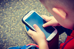 Little boy child playing games on mobile phone outdoor Royalty Free Stock Photography