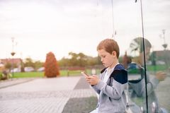 Little boy child playing mobile games on smartphone. In the park Stock Images