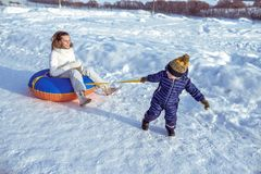 Little boy child pulls tubing over the rope. In blue overalls and hat. Woman mom sits on a toy. Happy playing in winter stock photography