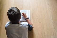 Little boy child reading a book. He lies on the floor. Royalty Free Stock Photo