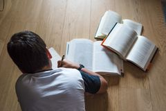 Little boy child reading a book. He lies on the floor. Stock Photography