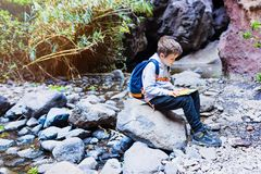 Little boy child reading map on mountain trail. Stock Photo