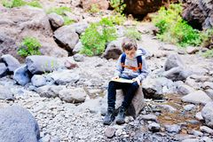 Little boy child reading map on mountain trail. Stock Photos