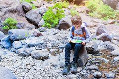 Little boy child reading map on mountain trail. Royalty Free Stock Photography