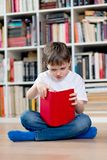 Little boy child reading a red book in the library. Royalty Free Stock Photography