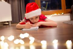 Little boy child in Santa Claus cap writing a letter to Santa. Dreaming about present and preparing wish list Stock Photo