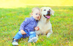 Little boy child sitting with Golden Retriever dog. On grass stock photos